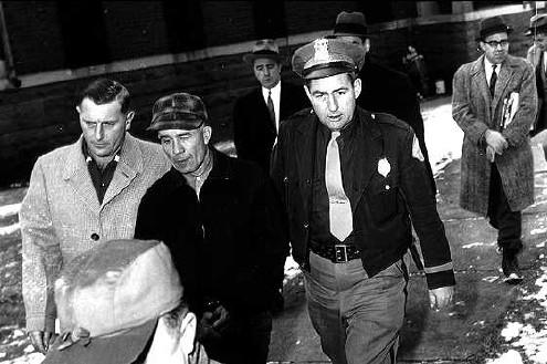 Эд Гин в сопровождении полицейских